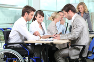 Man in wheelchair with colleagues in a meeting